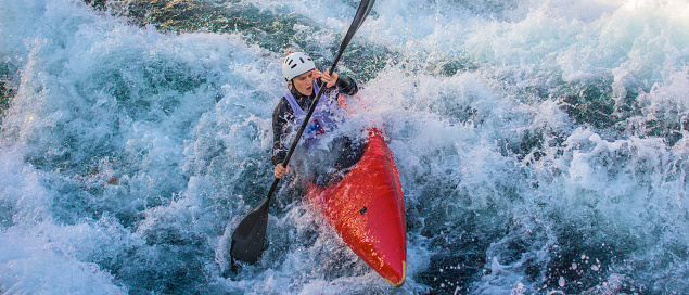 Woman rowing oar while enjoying kayaking in white water.