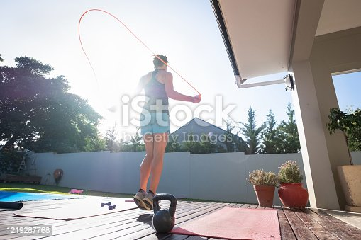 A women keeps fit at home by doing some jump rope. Active woman doing some exercise at home to keep fit and healthy