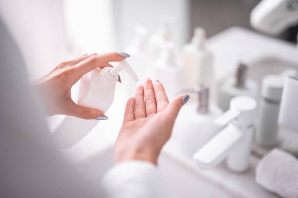 女性の維持腕をクリーニング用液体洗剤 - クリーム ストックフォトと画像