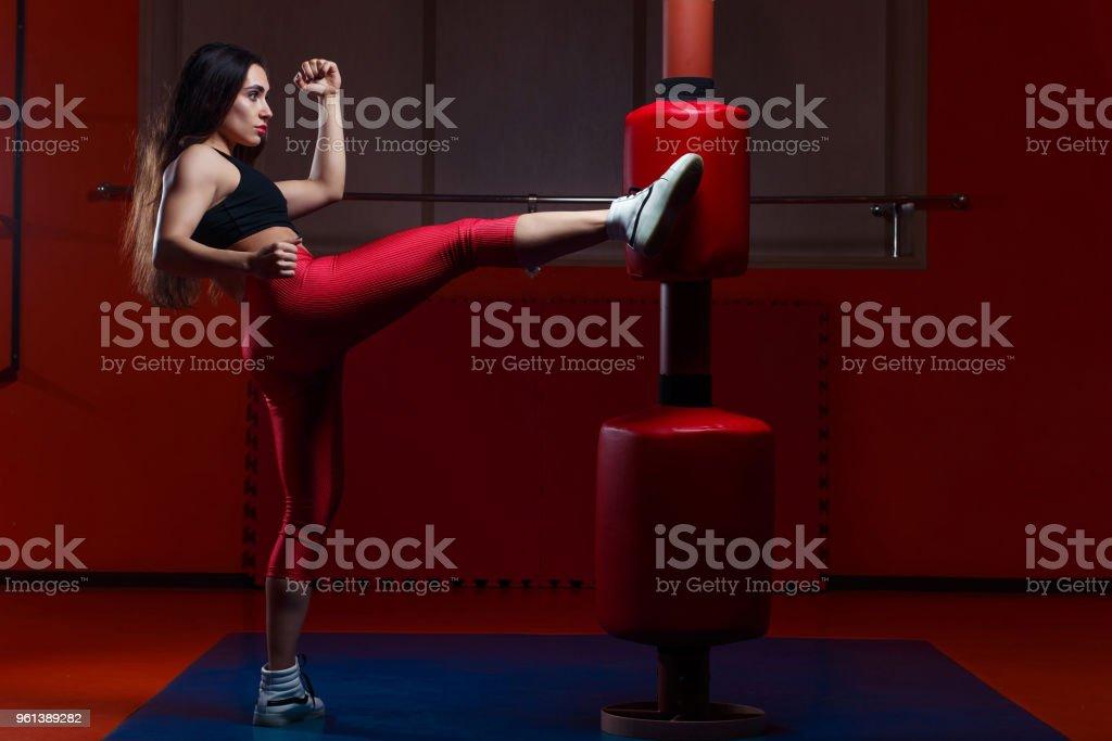 Woman kickboxing, hitting a punching dummy with a kick stock photo