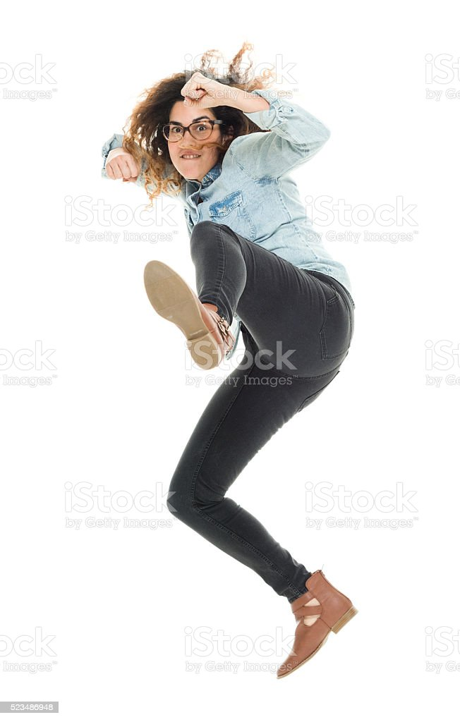 Woman kicking and about to fight stock photo