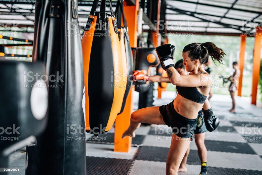 Woman kicking the punching bag stock photo