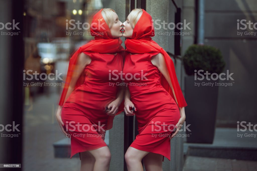Woman kisses her reflection. stock photo
