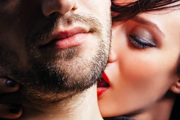 Mulher beijando o homem no pescoço - foto de acervo