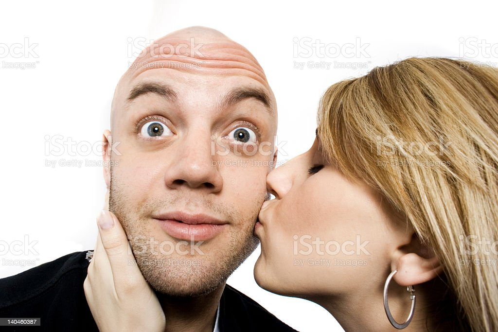 A woman kissing a man with a funny face stock photo