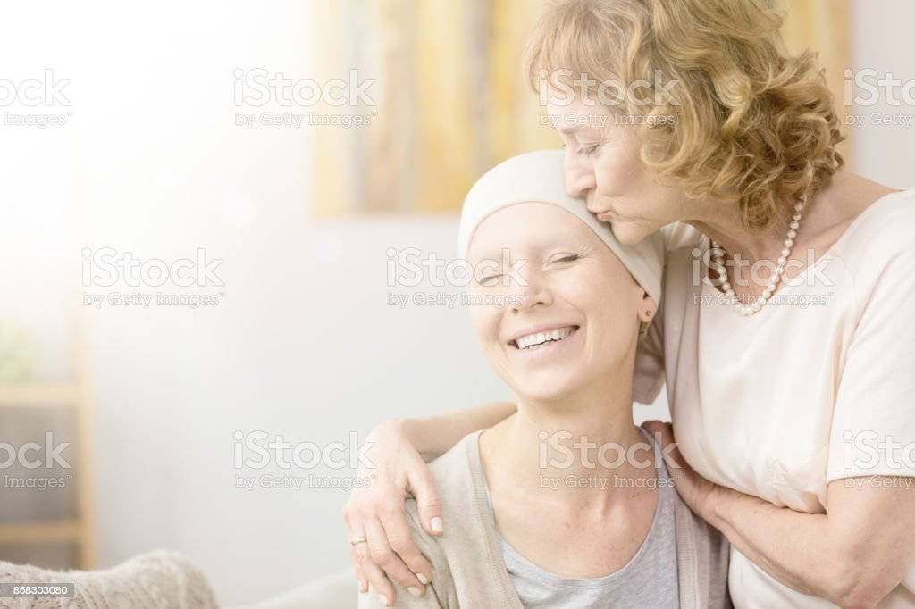 Woman kissing cancer survivor's temple stock photo