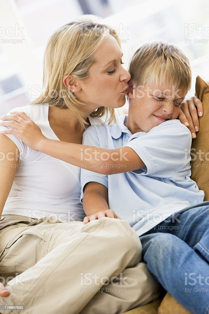 Woman kissing disgusted young boy in living room stock photo