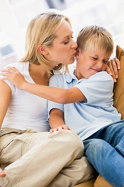 donna baciare persino giovane ragazzo in salotto - kids kiss embarrassed foto e immagini stock