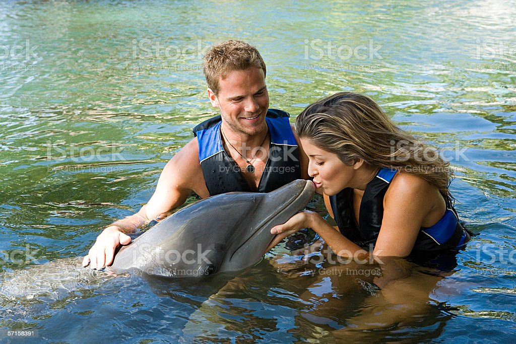 Woman kissing dolphin stock photo