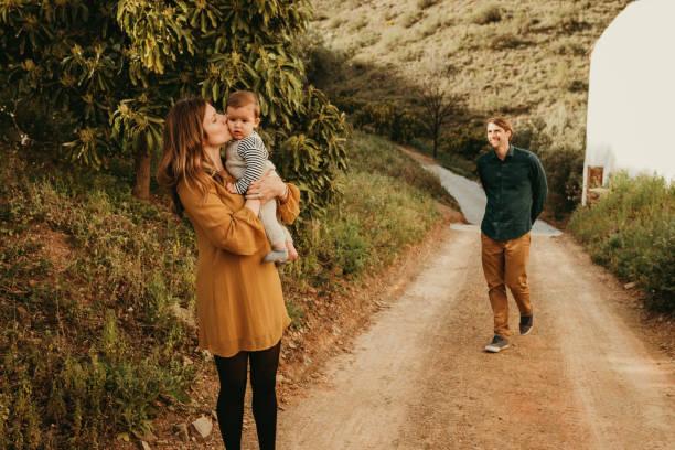 kvinna kysser sin son i naturen medan hennes man närmar sig dem med ett leende. - happy indie pop bildbanksfoton och bilder