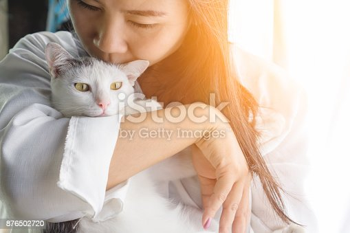 istock woman kissing her cute white cat with love 876502720