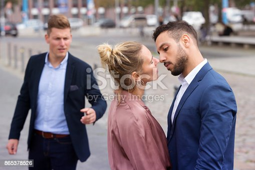 istock woman kissing man while another is upset 865378526