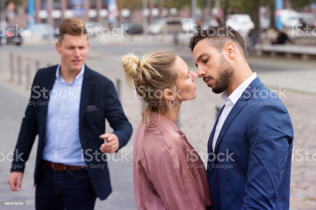Frau küssen während ein anderer Mann ist verärgert – Foto
