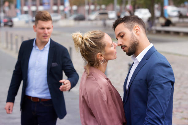 woman kissing man while another is upset stock photo