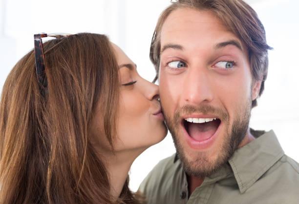 woman kissing man with beard on the cheek - brunette woman eyeglasses kiss man foto e immagini stock