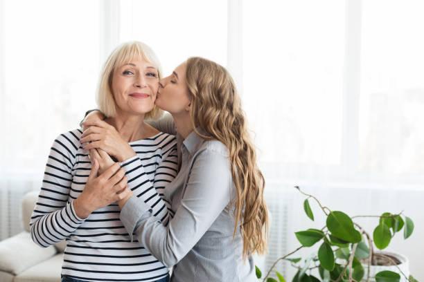 mujer besando madre mayor en la mejilla - hija fotografías e imágenes de stock