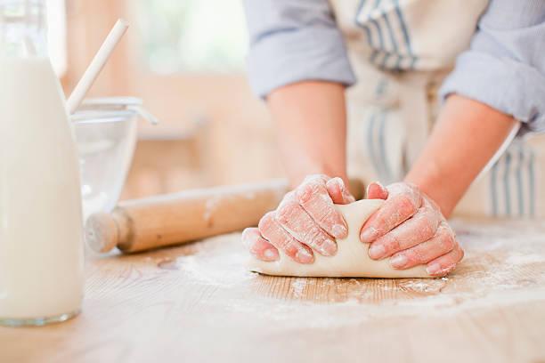 donna, impastare pasta sul tavolo di cucina - impastare foto e immagini stock