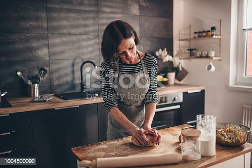 istock Woman kneading dough on the wooden table 1004500092