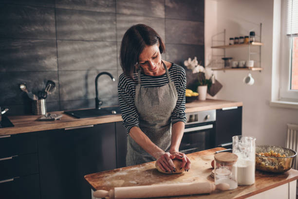 Woman kneading dough on the wooden table Woman standing in the kitchen by the old wooden table and kneading dough kneading dough stock pictures, royalty-free photos & images