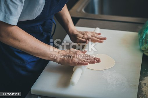 istock Woman kneading dough with rolling pin on white kitchen table - Stock photo 1175542293