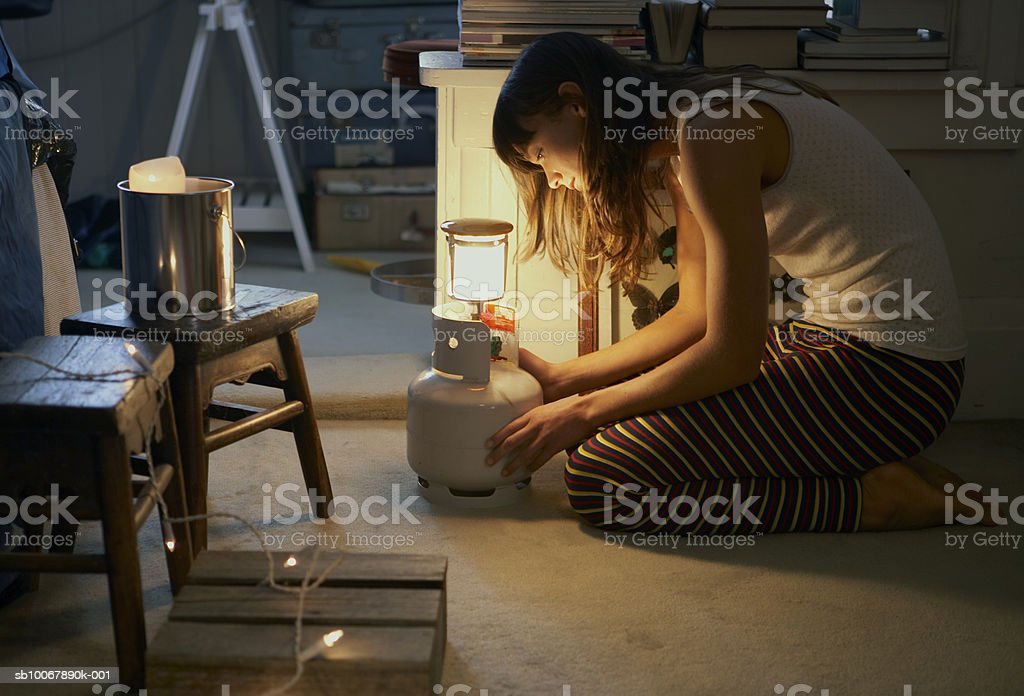 Woman kneeling by illuminated lamb, side view royalty free stockfoto