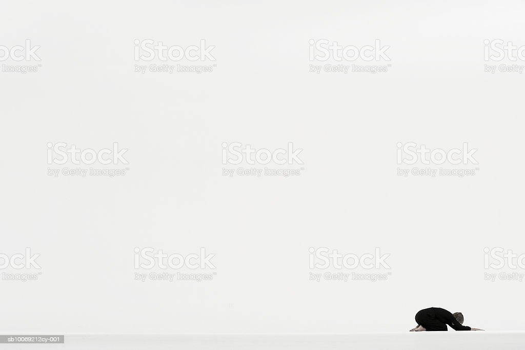 Woman kneeling on ground in distance against white background, side view royalty-free stock photo