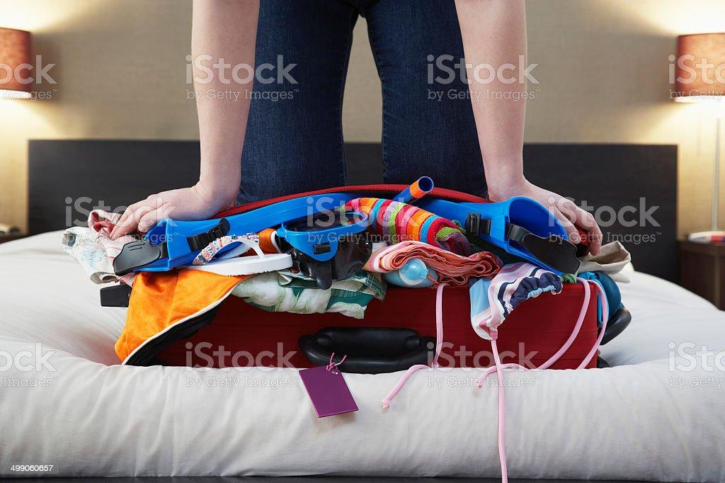Woman Kneeling On Overstuffed Suitcase stock photo