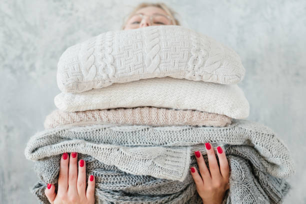 woman knitted plaid blanket cozy winter home decor woman holding big stack of knitted plaids and blankets. cozy and warm winter home decor sweater stock pictures, royalty-free photos & images