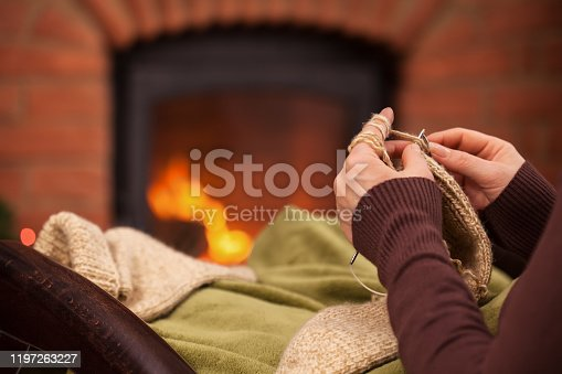 Woman knitting by the fireplace relaxing in armchair - closeup on hands