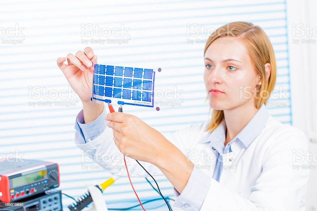 Woman laboratory assistant tests film  solar cells stock photo