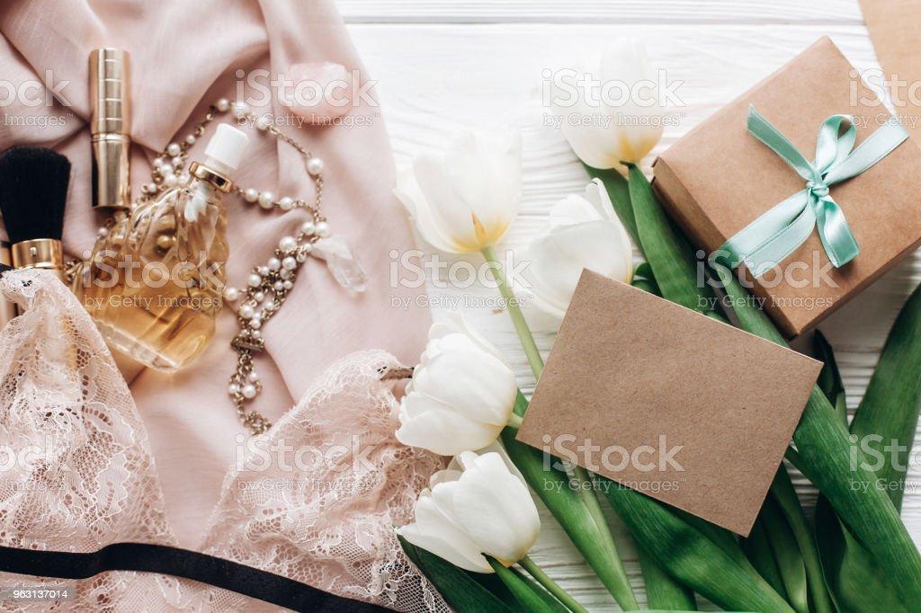 kvinna spets underkläder smycken och parfym presentera på mjukt tyg och tulpaner med tomma gratulationskort på vit rustik bakgrund. platt låg flicka essentials för en semester. Womens dag - Royaltyfri Behå Bildbanksbilder