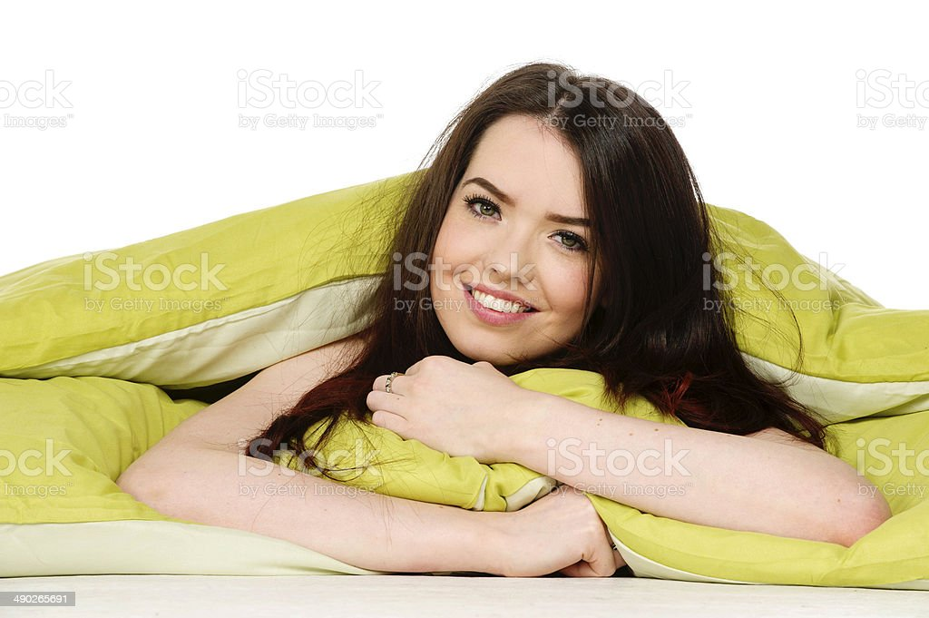 Woman laid in a green bed smiling stock photo