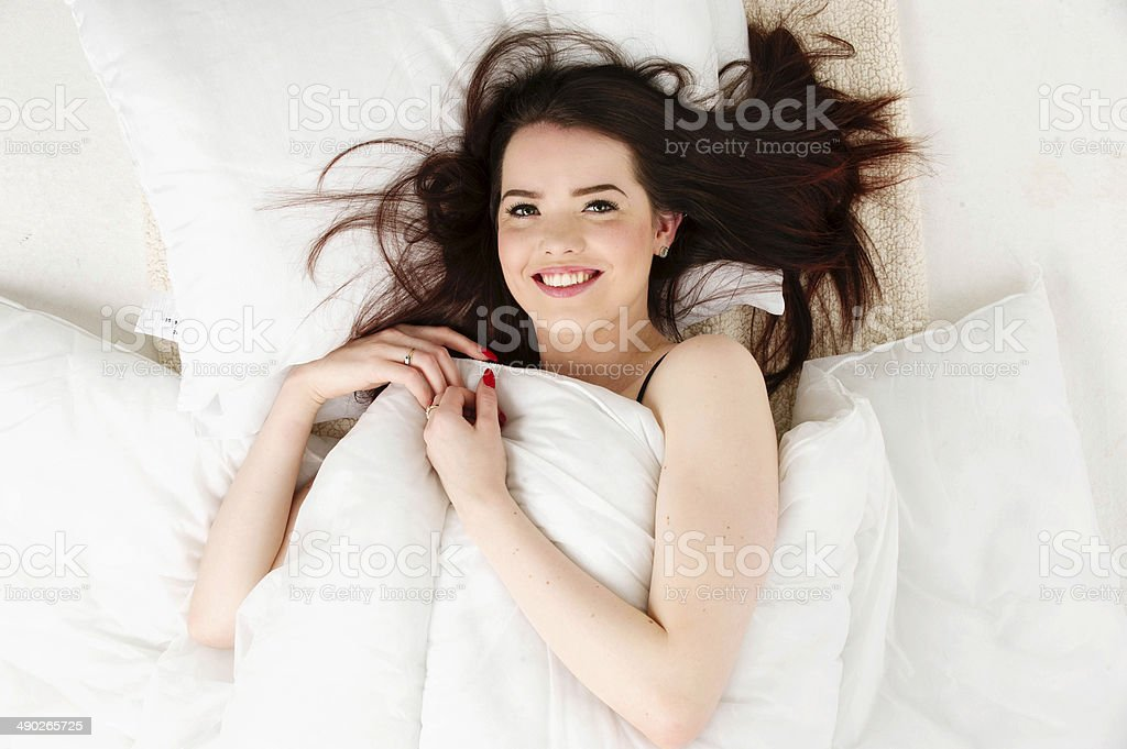 Woman laid in bed looking up stock photo