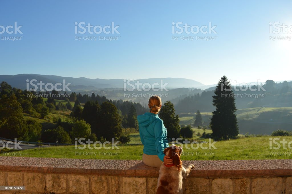 Woman looking the landscape in a mountain park with a dog