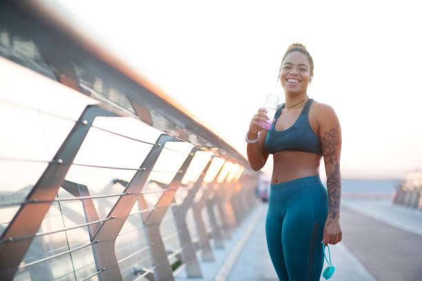 frau lacht nach dem laufen am morgen beim trinken - damen leggings übergrößen stock-fotos und bilder