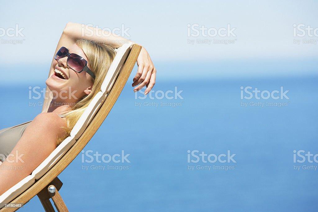 Mulher rir e encostado na Cadeira Dobrável ao ar livre foto de stock royalty-free