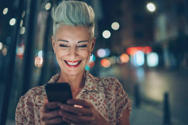 女人晚上在戶外嘲笑一條消息 - 僅一名中年女子 個照片及圖片檔