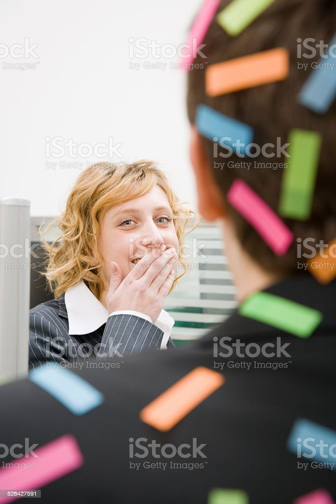 Woman Laughing at Man in Office stock photo