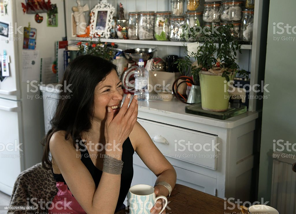 Woman laughing in kitchen royalty free stockfoto