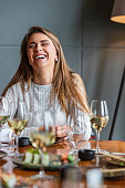 Woman laughing in a sushi restaurant on a business lunch