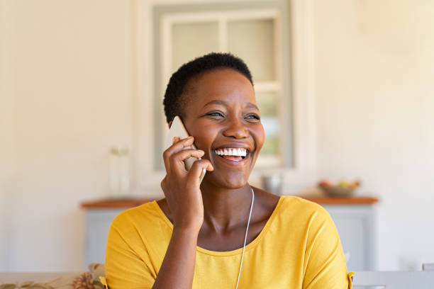 Woman laughing while talking on phone Smiling african american woman talking on the phone. Mature black woman in conversation using mobile phone while laughing. Young cheerful lady having fun during a funny conversation call. black woman stock pictures, royalty-free photos & images
