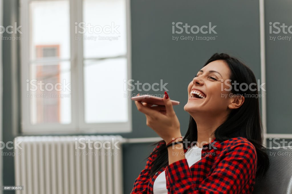 Woman laughing while talking on speakerphone. stock photo