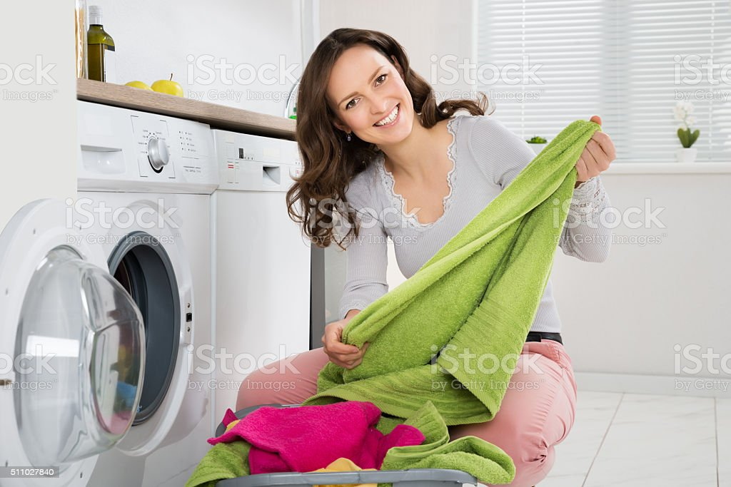 Woman Laundering Clothes In Washer stock photo