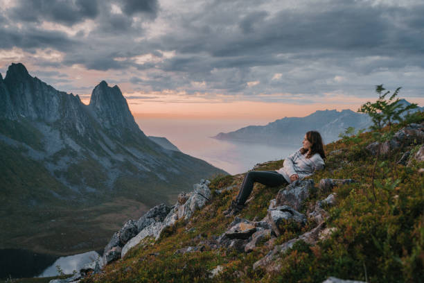 Woman laying and looking at scenic view of Senja stock photo