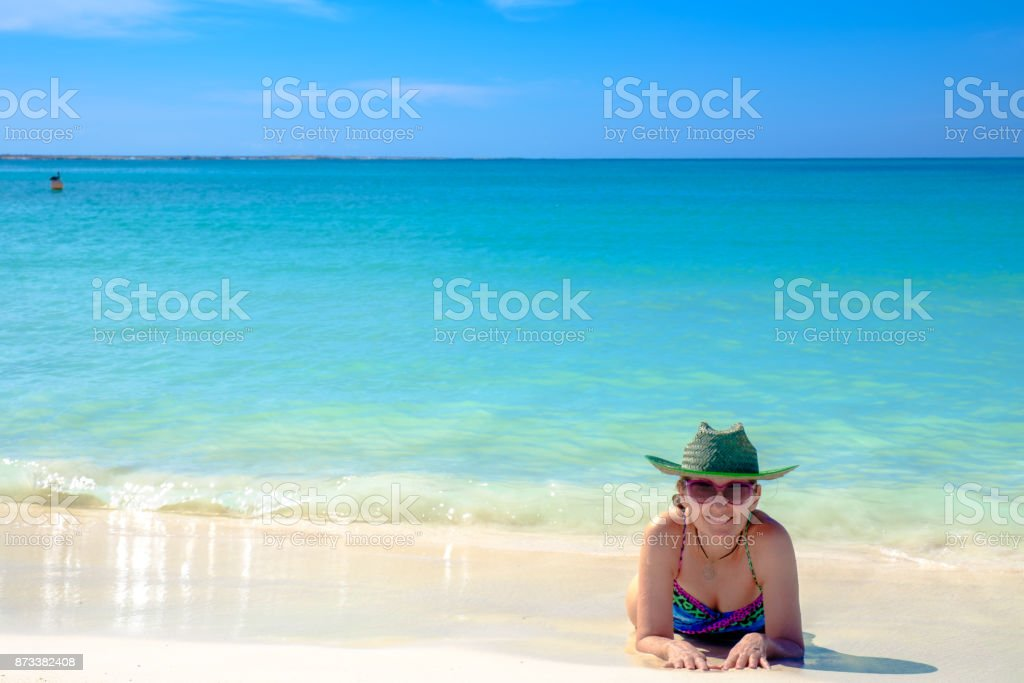 Woman laying at the beach on a sunny day stock photo
