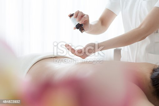 Happy woman laying face-down while receiving a massage with aromatic oil