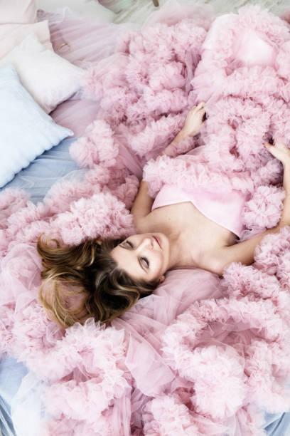 frau, die verlegung in eine lange blass rosa geraffte kleid - tüllkleid stock-fotos und bilder