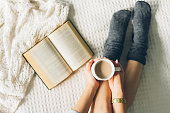istock woman laying in bed and read book with cup if coffee. 853965252