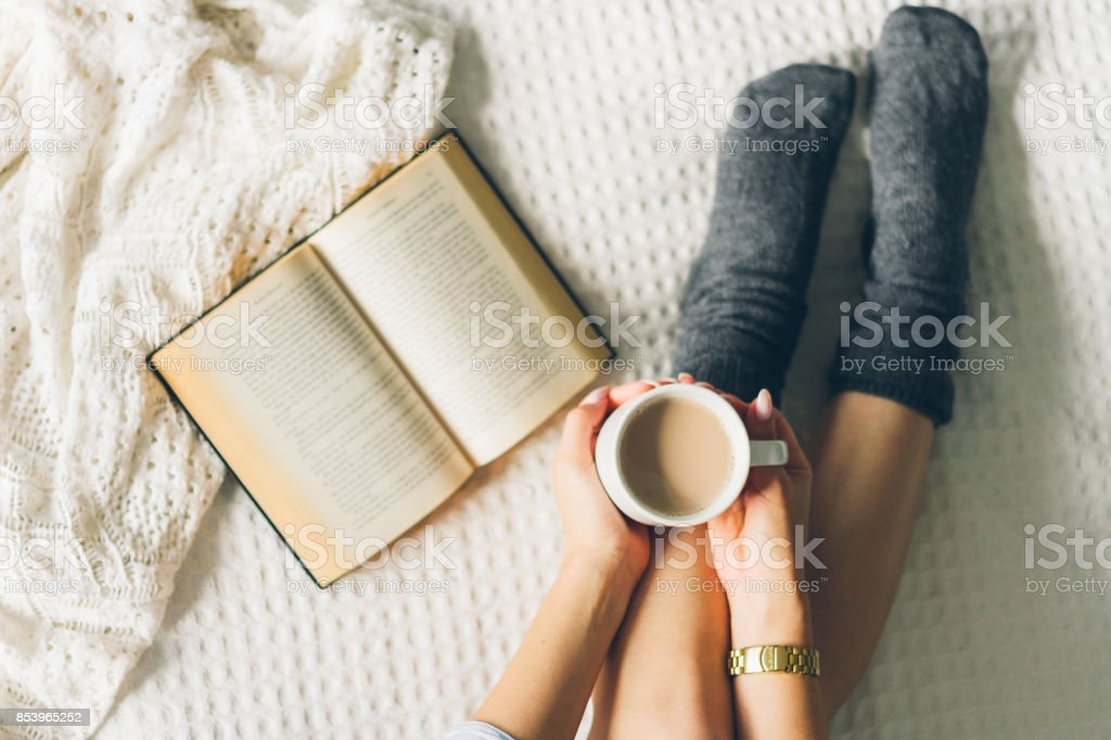 woman laying in bed and read book with cup if coffee. stock photo
