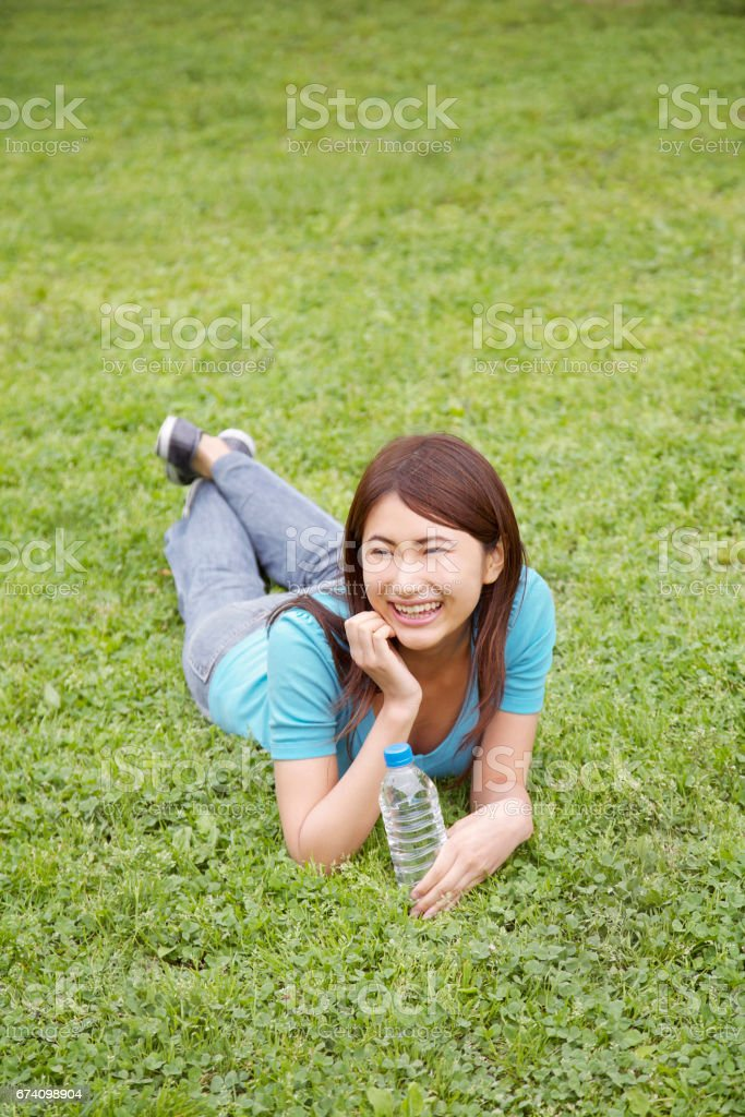 Woman laying in the grass stock photo